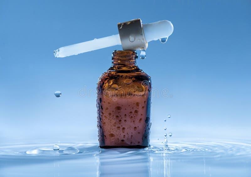 在大海背景的润湿的反年龄血清与吸移管和水飞溅 免版税库存图片