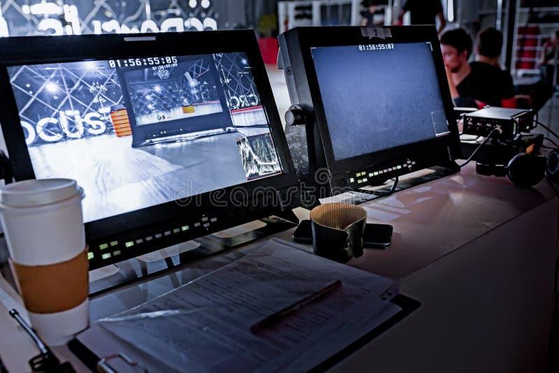 在大演播室和显示器设置的在幕后电视电影录影影片射击生产人员队和照相机 图库摄影