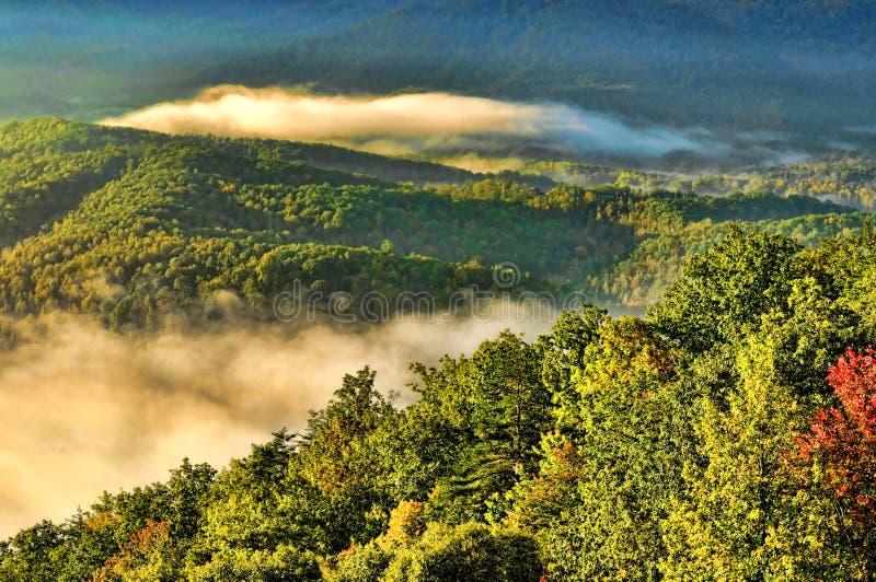 在大烟雾弥漫的山脉的日出 库存图片