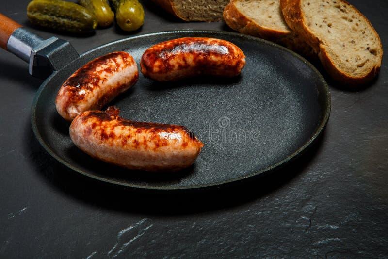 在大煎锅油煎的特写镜头开胃红润水多的香肠 库存照片