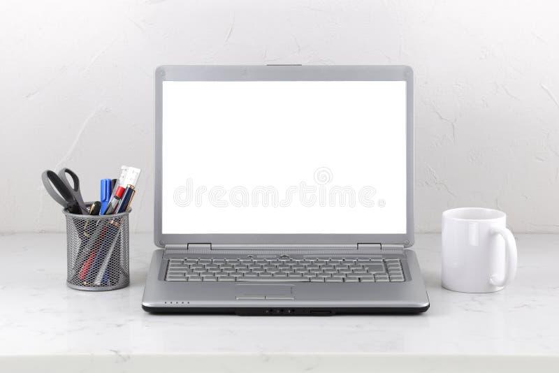 在大理石办公桌咖啡杯和笔的膝上型计算机 与裁减路线的白色屏幕模板 库存照片