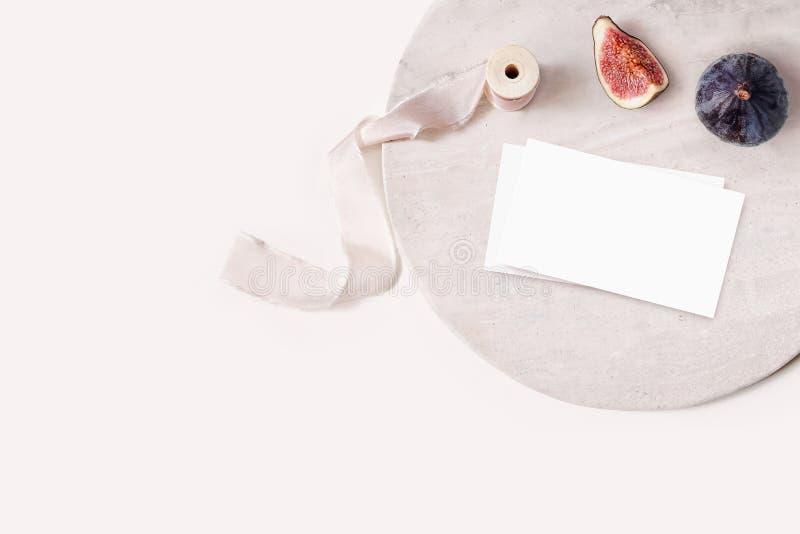 在大理石板材的空白的白色名片大模型 在裸体桃红色背景的成熟的紫色无花果果子和丝绸丝带 库存照片