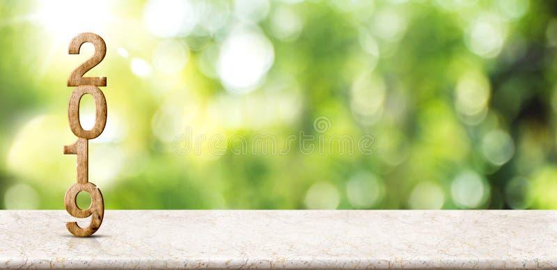 在大理石桌上的新年2019木数字3d翻译在迷离抽象绿色bokeh有太阳光芒背景,嘲笑横幅空间 免版税库存图片