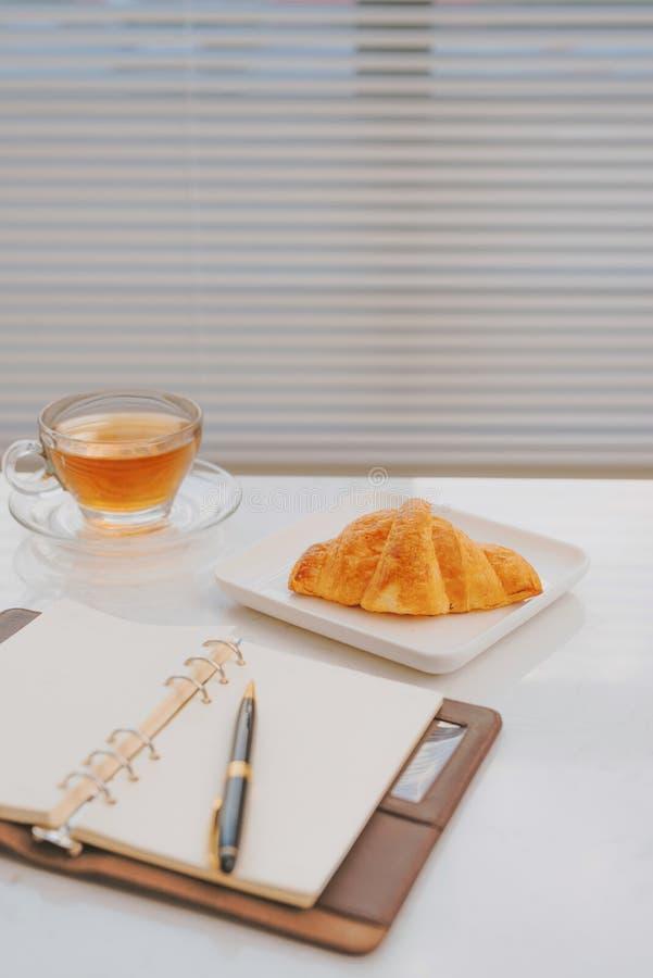 在大理石桌咖啡的企业工作与新月形面包面包店 免版税库存图片