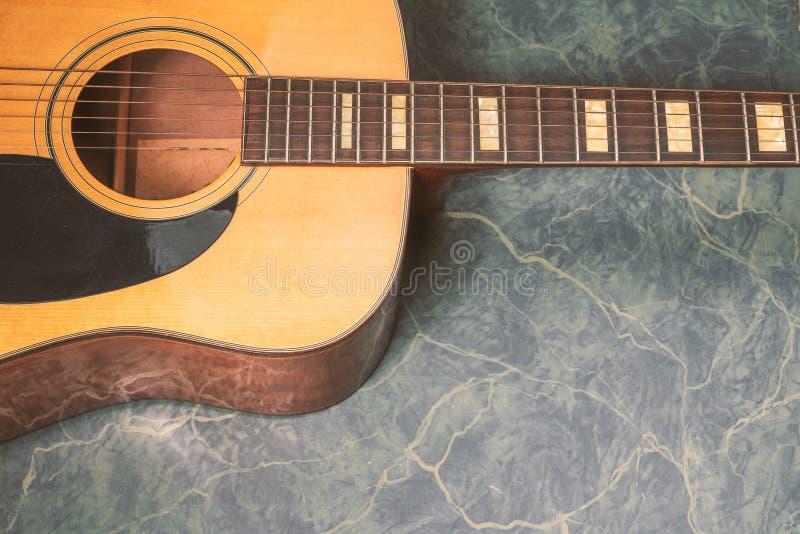 在大理石背景的声学吉他细节 免版税图库摄影