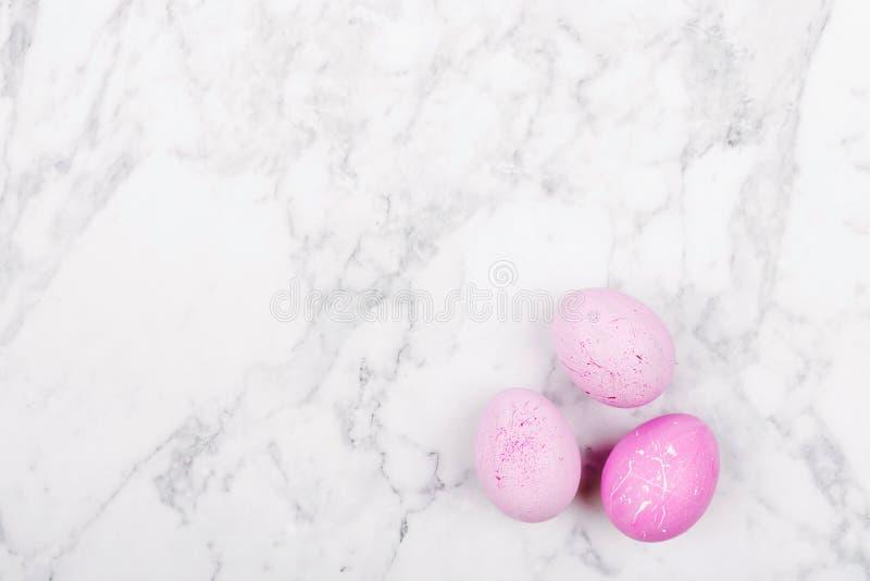 在大理石背景的时髦桃红色复活节彩蛋 图库摄影