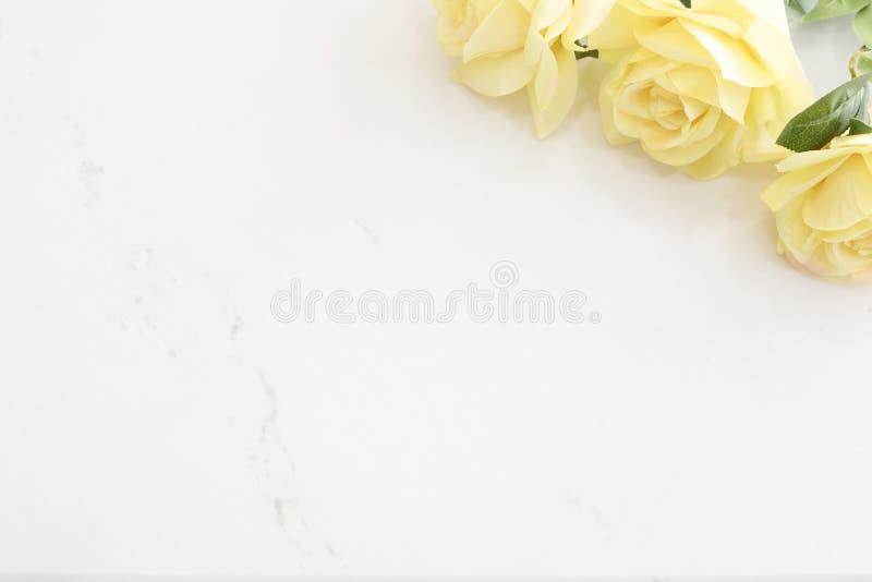 在大理石背景,黄色玫瑰边界的黄色玫瑰  与黄色花的花卉框架在木背景 被称呼的marketi 库存照片