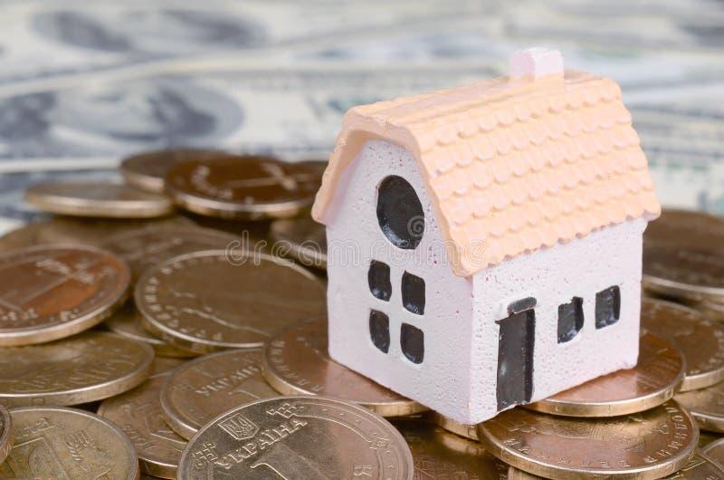 在大硬币堆的微型房子模型在作为背景的许多美金 库存图片