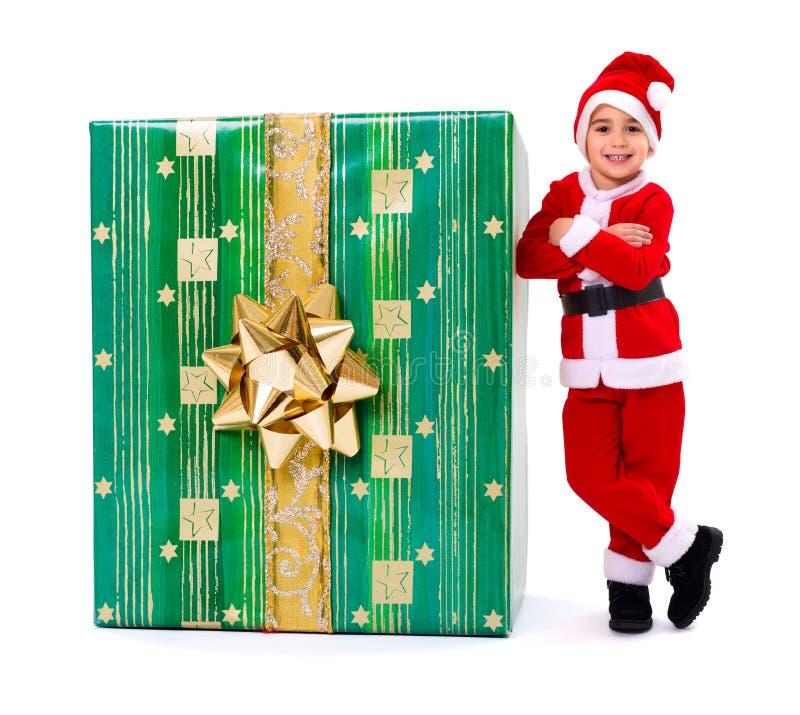 在大礼物旁边的一点圣诞节男孩 库存照片