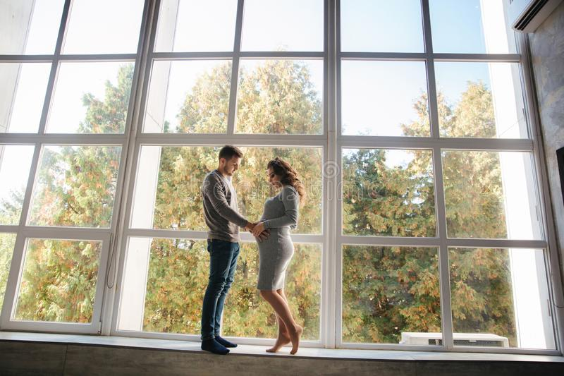 在大窗口前面的美好的夫妇立场在演播室 她的丈夫孕妇 库存照片