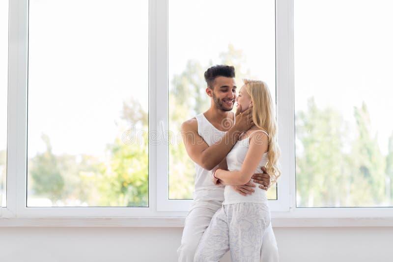 在大窗口容忍亲吻,愉快的西班牙男人和妇女附近的年轻美好的夫妇立场 图库摄影