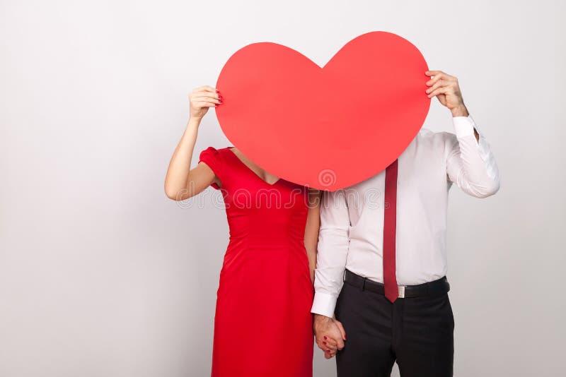 在大红色心脏后的未知的夫妇捉迷藏 免版税库存照片