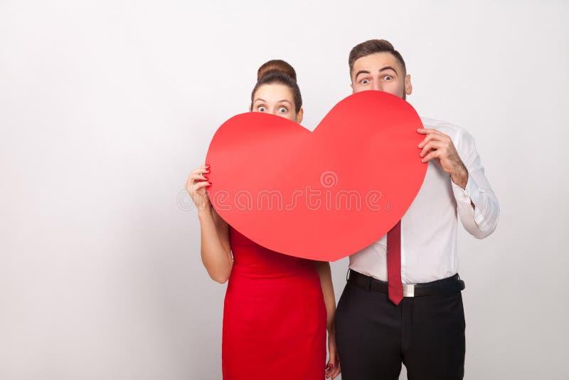 在大红色心脏后的滑稽的夫妇捉迷藏 库存照片