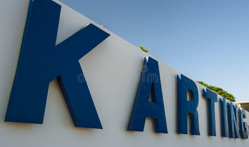 在大蓝色信件的Karting在白色墙壁上 库存照片