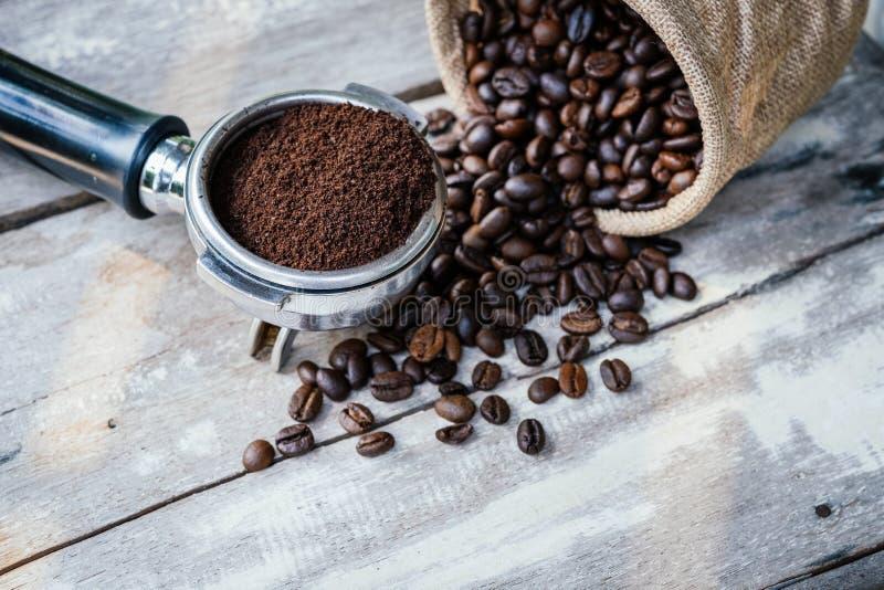 在大袋和portafilter的咖啡豆在老白色木桌上 免版税库存照片