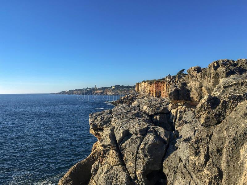 在大西洋海岸的美好的多岩石的海滩风景在阳光天空蔚蓝和波浪背景 库存照片