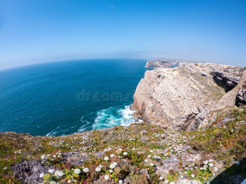 在大西洋西海岸的峭壁在萨格里什,阿尔加威,葡萄牙 在水的天际反对清楚的天空蔚蓝 图库摄影