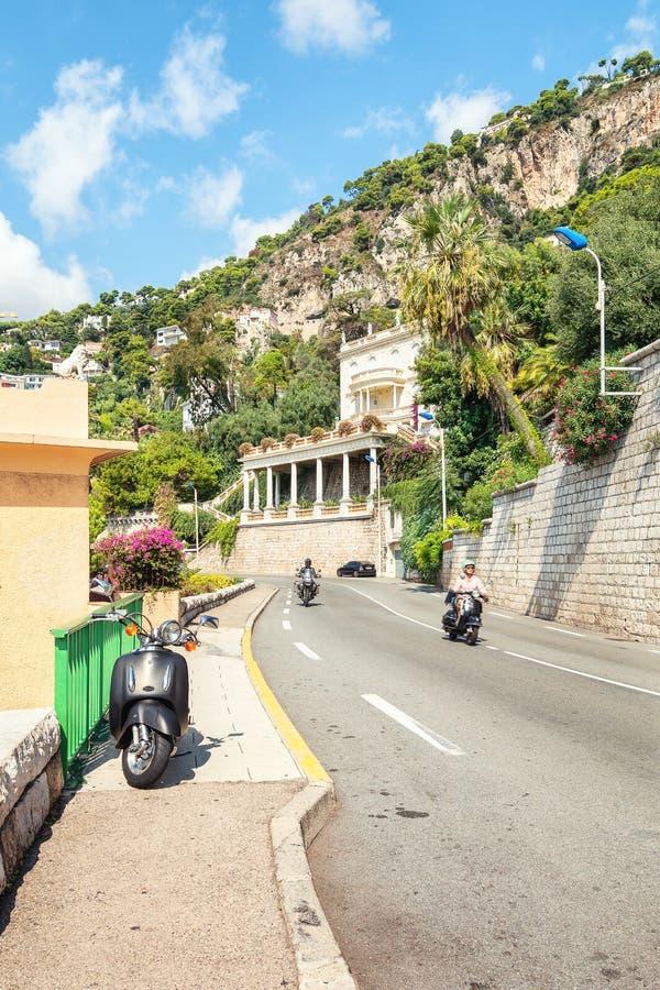 在大道拿破仑三世的一个摩托车骑士和滑行车车手i 库存图片