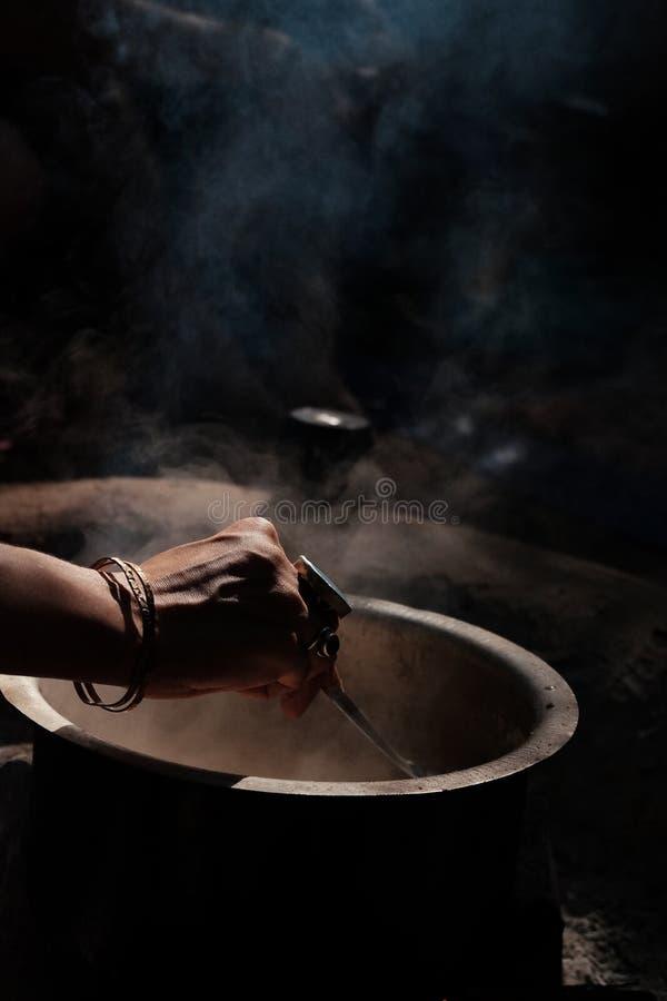 在大锅的手混合的食物 免版税库存图片