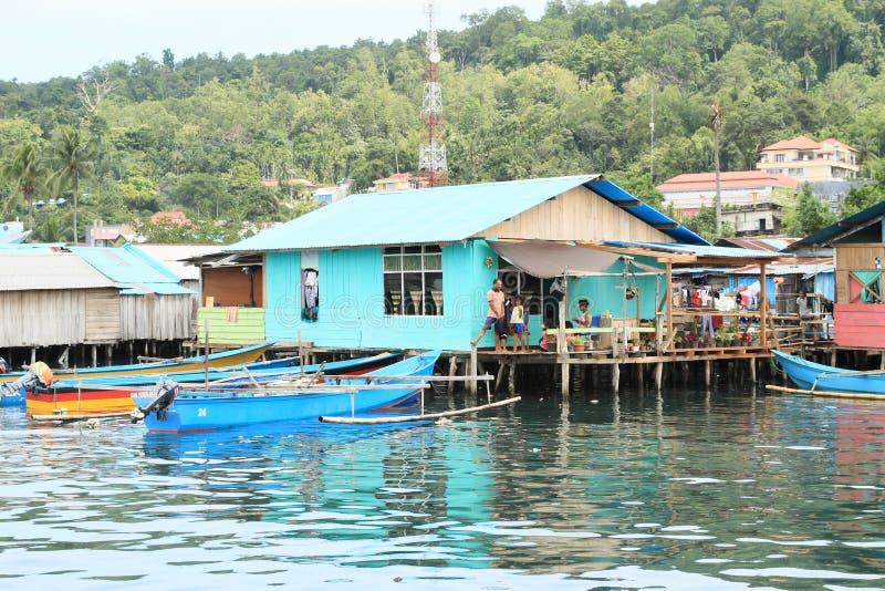 在大阳台的家庭在渔夫村庄在曼诺瓦里 免版税库存照片