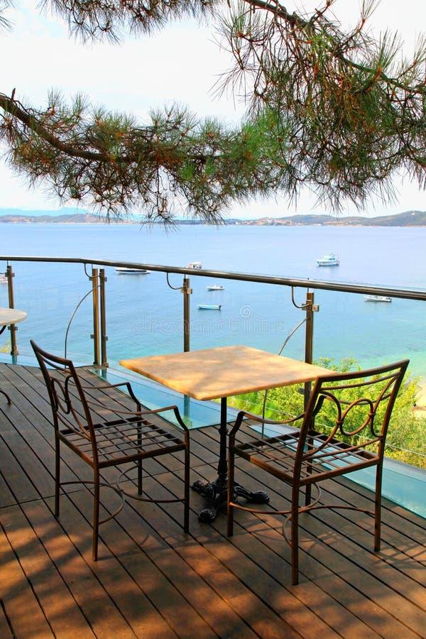 在大阳台的表和铁椅子与海观看(希腊) 免版税库存照片