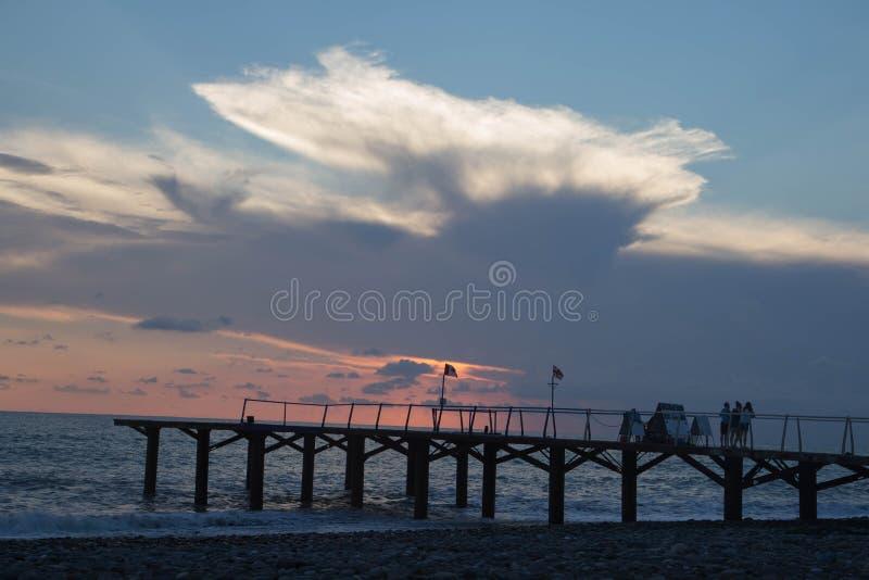在大阳台船坞或码头的太阳设置 跳船海和多云天空背景,日落 库存照片