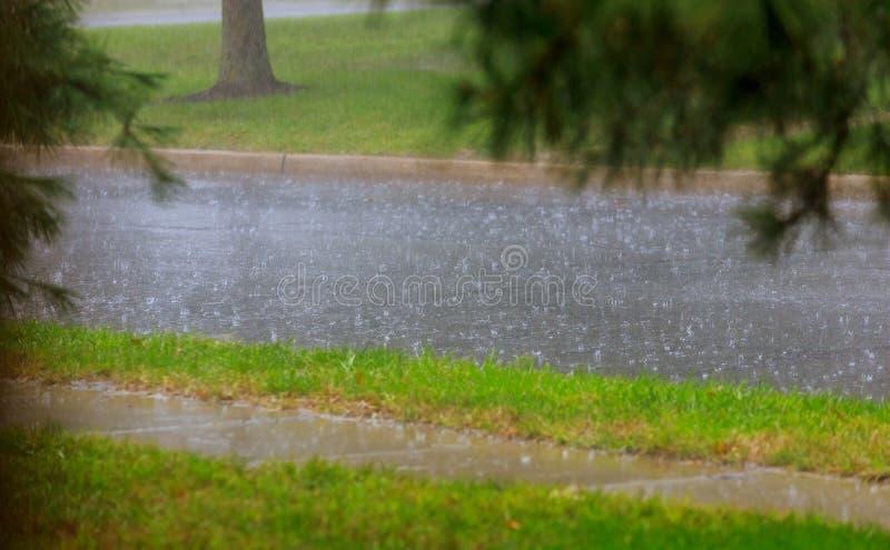 在大雨期间被充斥的城市道路 在水水坑的雨珠 恶劣天气 图库摄影
