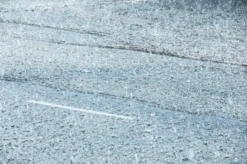 在大雨期间被充斥的城市道路 在水水坑的雨珠 免版税库存图片