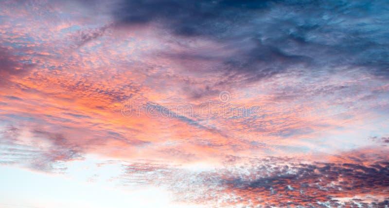 在天空与明亮的桃红色,蓝色,红色,在澳洲内地的桔子的五颜六色的云彩在美术的澳大利亚- 库存图片