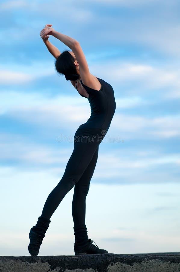 在天空女子瑜伽的蓝色跳舞 库存图片