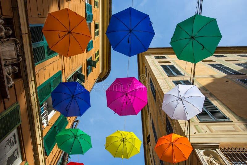 在天空的多彩多姿的伞在街道上在热那亚,意大利的中心, 库存照片