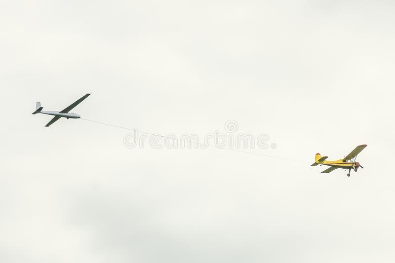 在天空的小轻引擎体育飞机飞行在绳索拉扯滑翔机飞机 库存照片