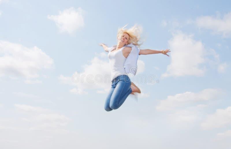 在天空的愉快的年轻秀丽 免版税库存图片