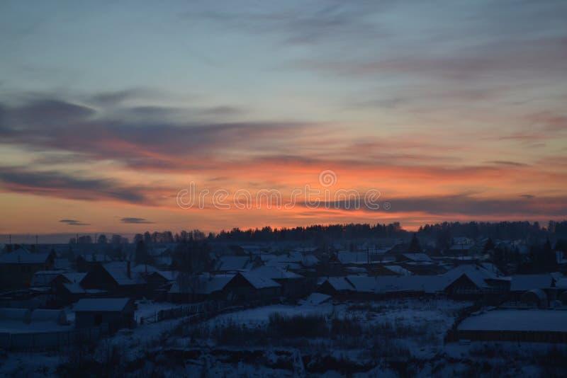 在天空的日落在冬天俄国村庄 库存图片