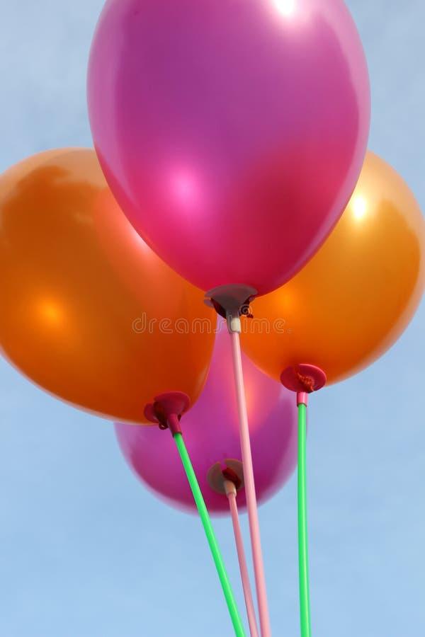 在天空的桃红色和橙色气球 免版税库存照片