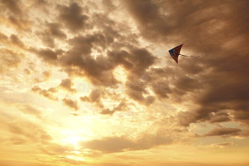 在天空的风筝飞行与在日落的云彩 库存照片