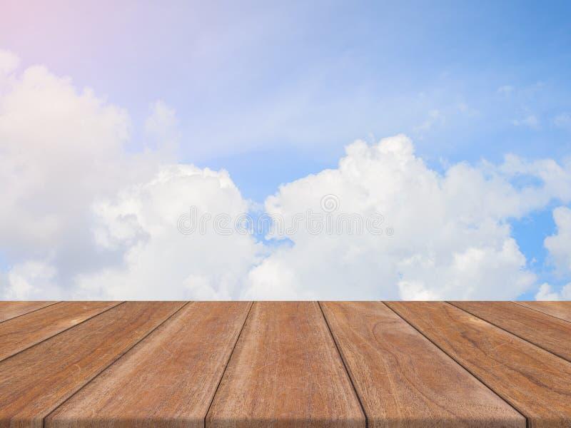 在天空背景前面的葡萄酒木板空的桌 在天空的透视木地板-能为显示或蒙太奇使用 库存图片
