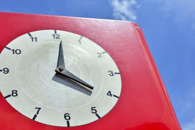 在天空背景的老红色时钟 库存照片