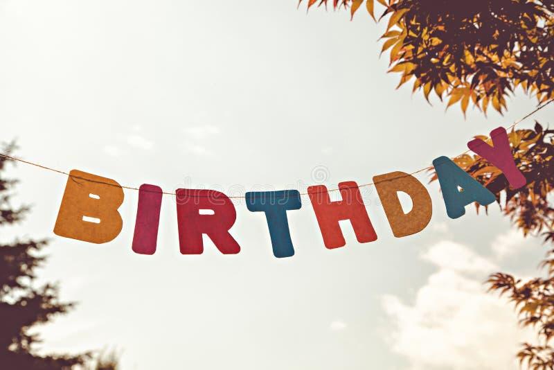 在天空背景的色的信件生日 免版税库存照片