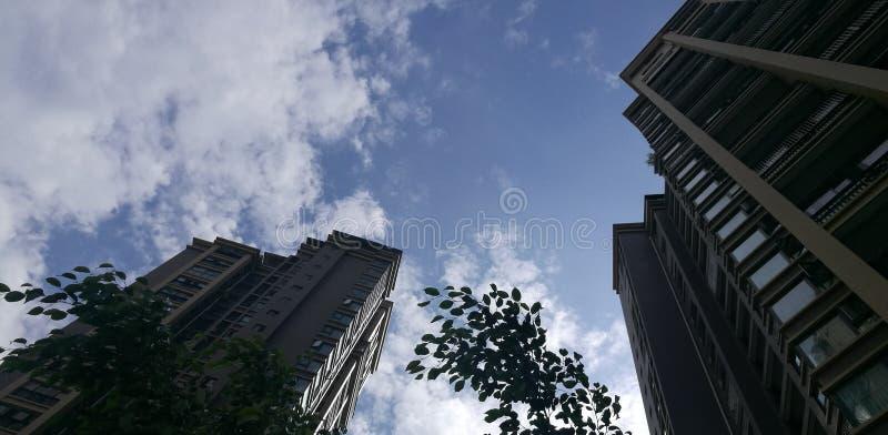 在天空蔚蓝和白色云彩下的高层建筑物 免版税库存照片