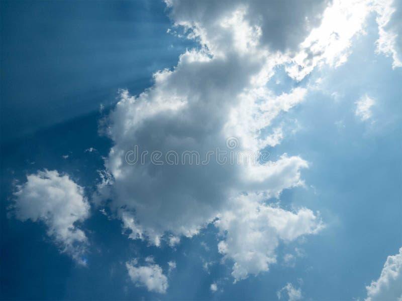 在天空蔚蓝的云彩,来通过云彩的太阳光芒 免版税库存图片