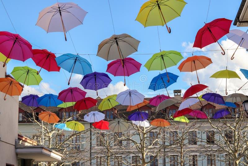 在天空蔚蓝的五颜六色的伞在老街道上在卡鲁日镇,日内瓦,瑞士邻里, 库存图片