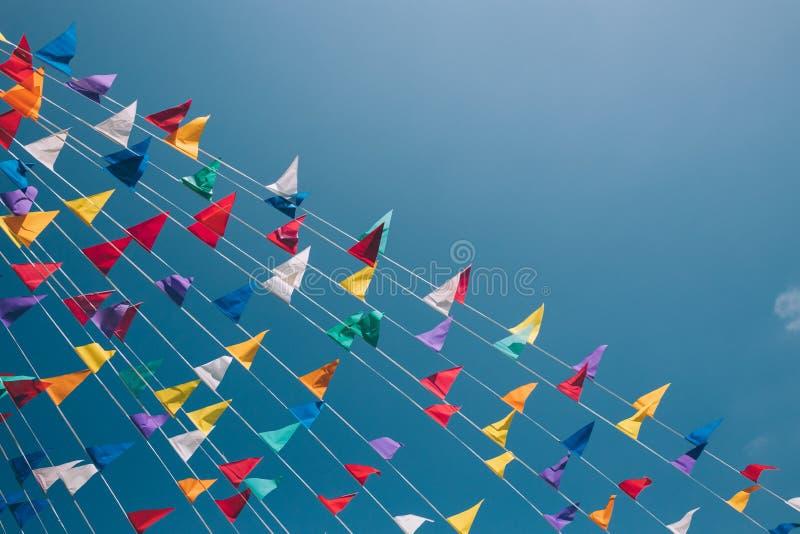 在天空蔚蓝的五颜六色的短打的旗子在背景 免版税库存图片