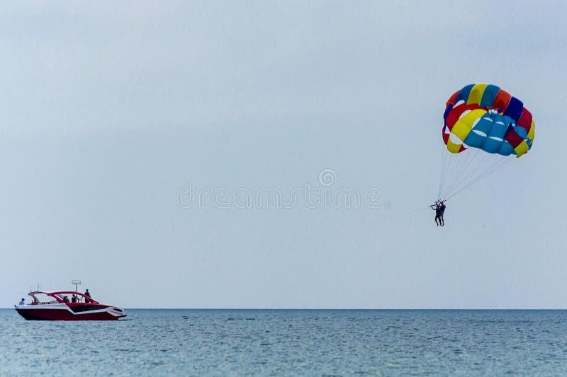 在天空蔚蓝的帆伞运动在有一红色汽艇拖曳的镇静海洋在降伞下暂停的人由鞔具 ??  免版税库存照片