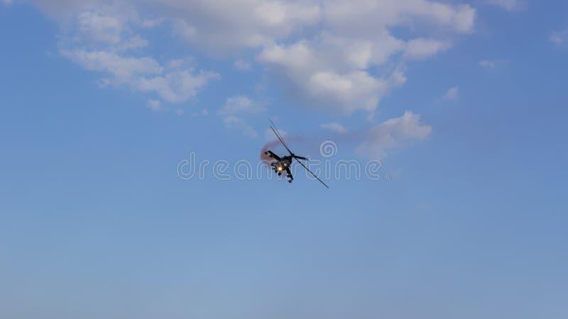 在天空蔚蓝的战斗直升机与乌云 免版税库存照片