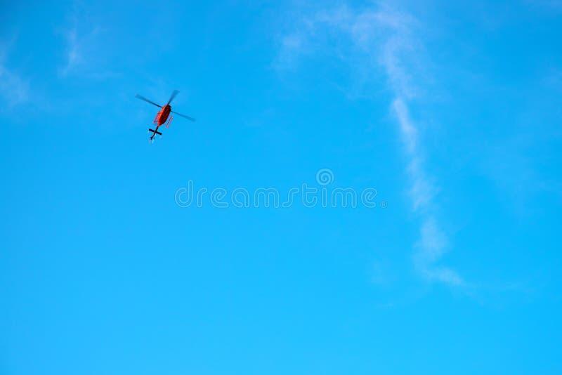 在天空蔚蓝的红色直升机 紧急情况服务直升机飞行 与文本地方的红色直升机横幅模板 免版税图库摄影