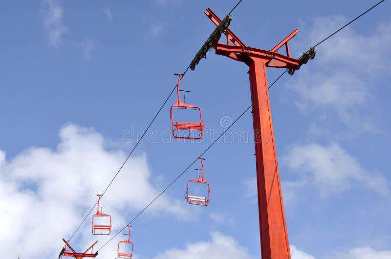 在天空蔚蓝的红色驾空滑车 免版税库存照片