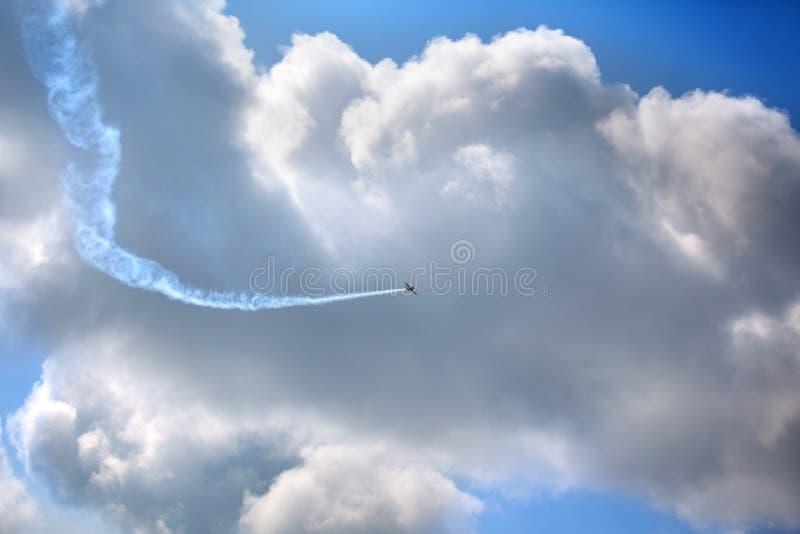 在天空蔚蓝的飞机和在天空的巨大的白色云彩背景上流 免版税库存照片