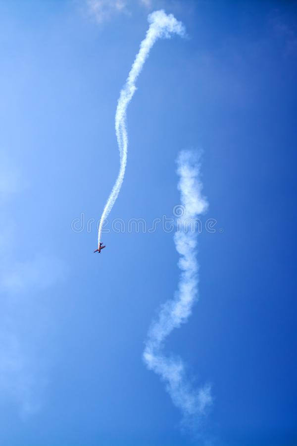 在天空蔚蓝背景上流的落的飞机在天空,倒下,图特技飞行桶式滚 免版税库存图片
