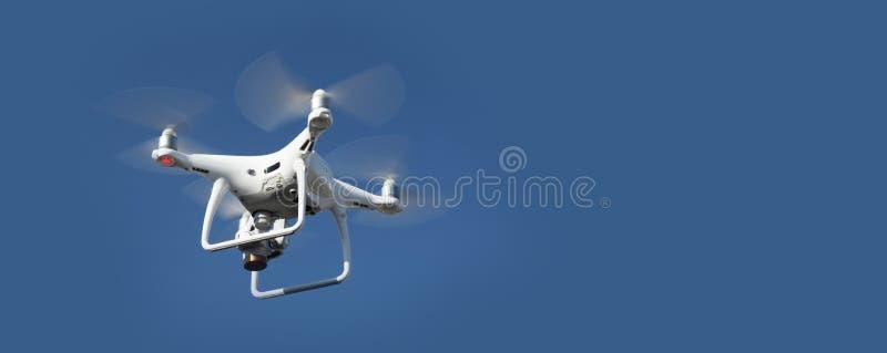 在天空蔚蓝背景的寄生虫 与照相机的遥控quadrocopter摄影的 飞行的机器人 免版税库存图片